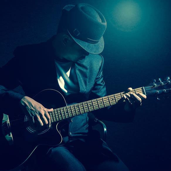 musician-playing-guitar-on-black